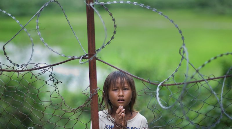 A little girl begs for money outside the barbed wire fence at the Killing Fields museum in Cambodia. The museum was a former school in Phnom Pehn used as a prison where Cambodians were interrogated, tortured, and murdered by the Khmer Rouge. The Khmer Rouge ruled Cambodia from 1975 to 1979.  While in power the Khmer Rouge murdered, worked to death, or killed by starvation close to 1.7 million Cambodians, or more than one-fifth of the countryÕs population.